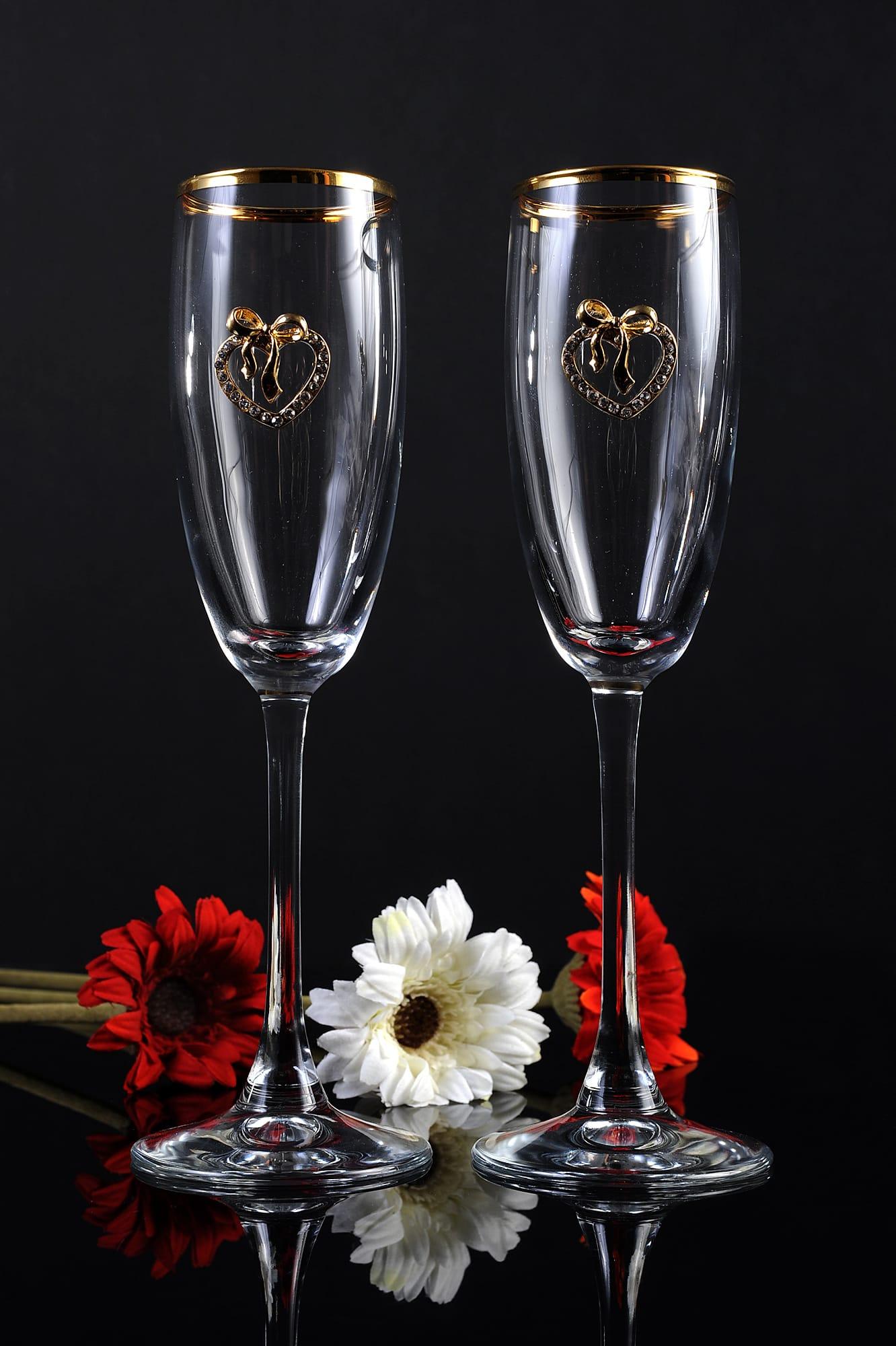 Прозрачные свадебные бокалы с золотистой отделкой по верху и сердечками на чаше.