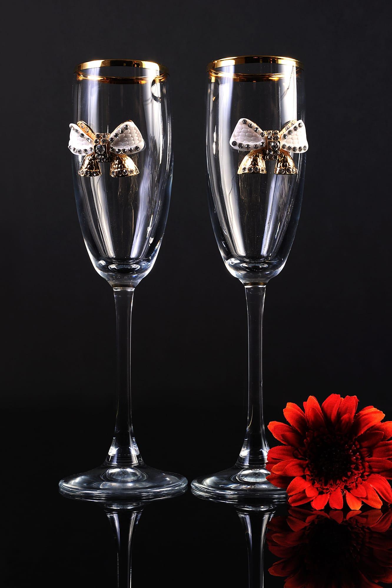Прозрачные свадебные фужеры, украшенные объемными бантиками и золотом по верху.