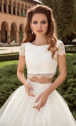 Пышное свадебное платье с укороченным топом с округлым вырезом и юбкой, покрытой кружевом.