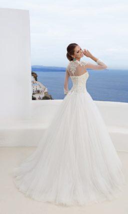 Пышное свадебное платье с фигурным вырезом и полупрозрачными рукавами длиной в три четверти.