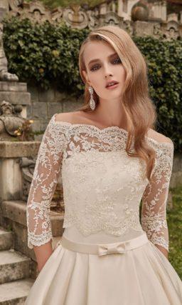 Атласное свадебное платье пышного кроя с фигурным портретным декольте и длинным рукавом.