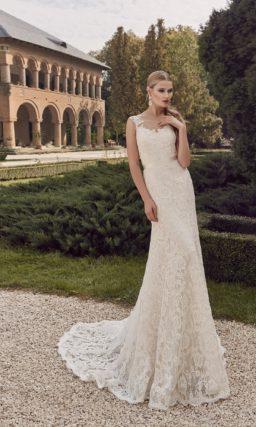 Свадебное платье цвета слоновой кости, облегающее фигуру изящной кружевной тканью.