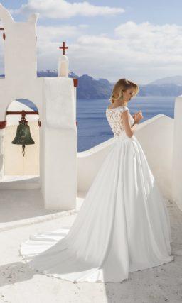 Утонченное свадебное платье с кружевным декором корсета, узким поясом из атласа и пышной юбкой.