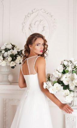 Нежное свадебное платье с полупрозрачной отделкой верха и завышенной линией талии.