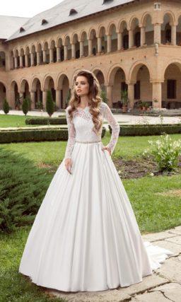 Свадебное платье с фигурным вырезом, длинным кружевным рукавом и атласной юбкой.