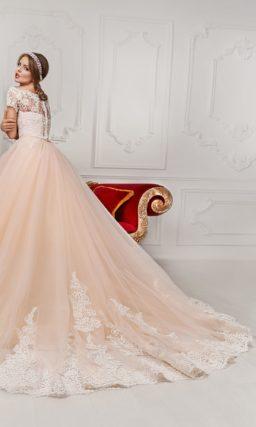 Персиковое свадебное платье пышного кроя с кружевным декором подола и длинным шлейфом.