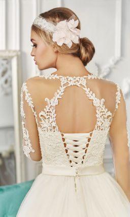 Кружевное свадебное платье с прозрачной отделкой верха и многослойным подолом.