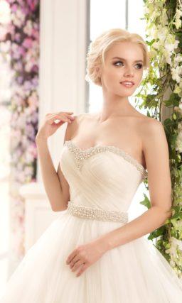 Безупречное свадебное платье пышного кроя с декором из драпировок и вышивки бусинами.