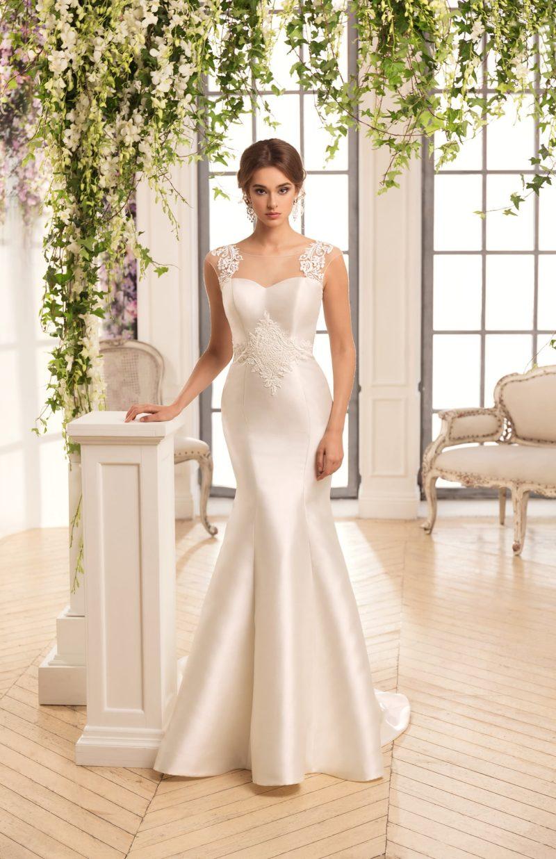 Атласное свадебное платье облегающего кроя, дополненное аппликациями на талии и лифе.
