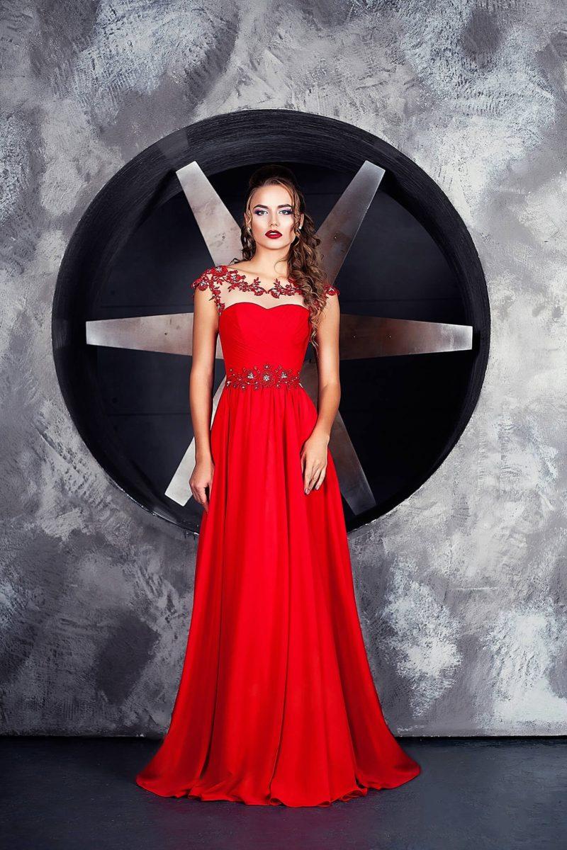 Эффектное вечернее платье алого цвета с аппликациями по тонкой вставке сверху.