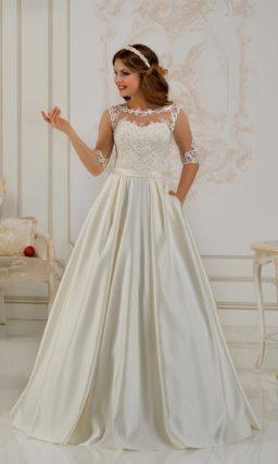 Сияющее свадебное платье с атласной юбкой «трапеция» и закрытым кружевным верхом.