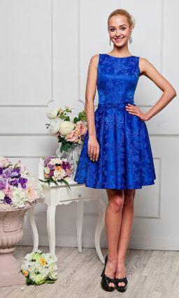 Изысканное вечернее платье из синей жаккардовой ткани, с круглым вырезом и юбкой до колена.