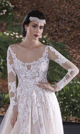 Впечатляющее свадебное платье пышного кроя оттенка слоновой кости, украшенное белым кружевом.