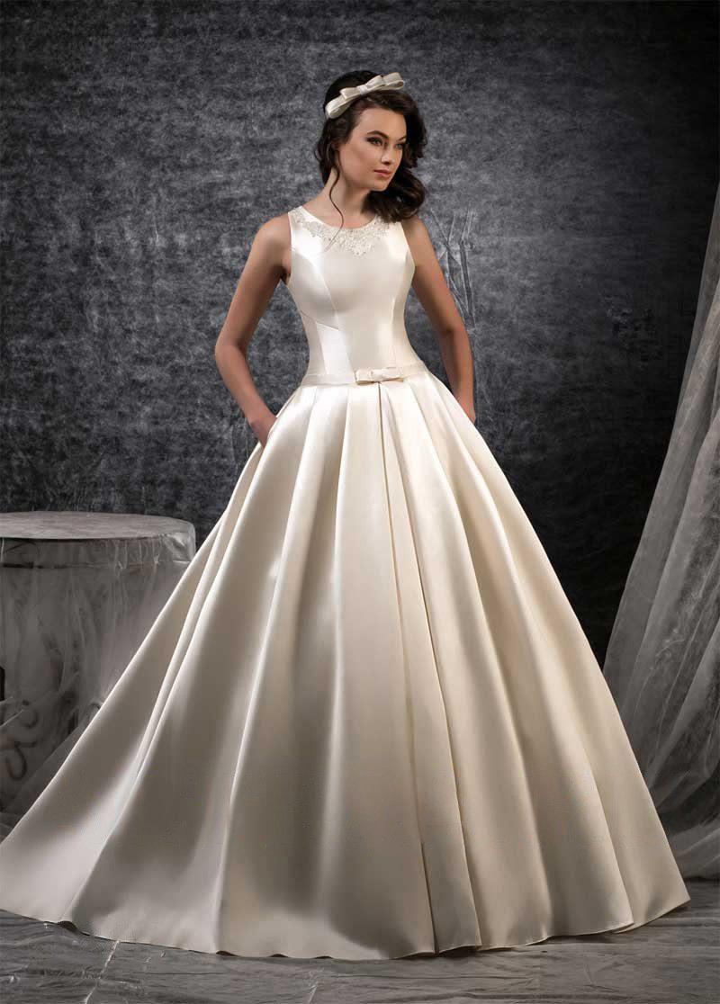 Атласное свадебное платье цвета слоновой кости со скрытыми карманами на пышной юбке.