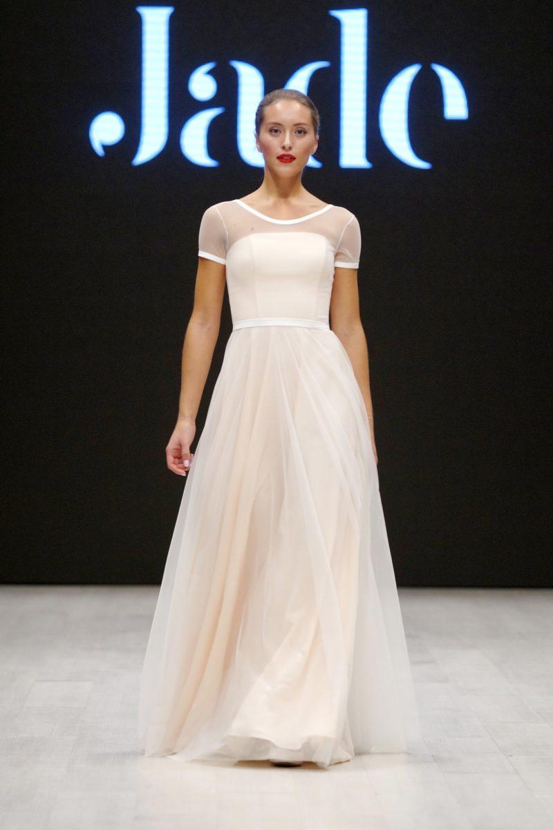Кремовое свадебное платье прямого кроя с тонким коротким рукавом.