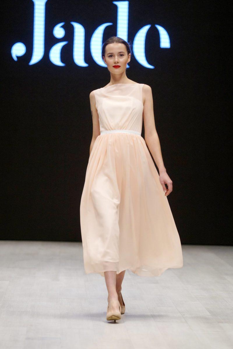 Кремовое свадебное платье чайной длины с изящным закрытым лифом.