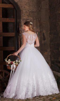 Пышное свадебное платье с кружевными аппликациями по низу подола и тонкой вставкой на спинке.