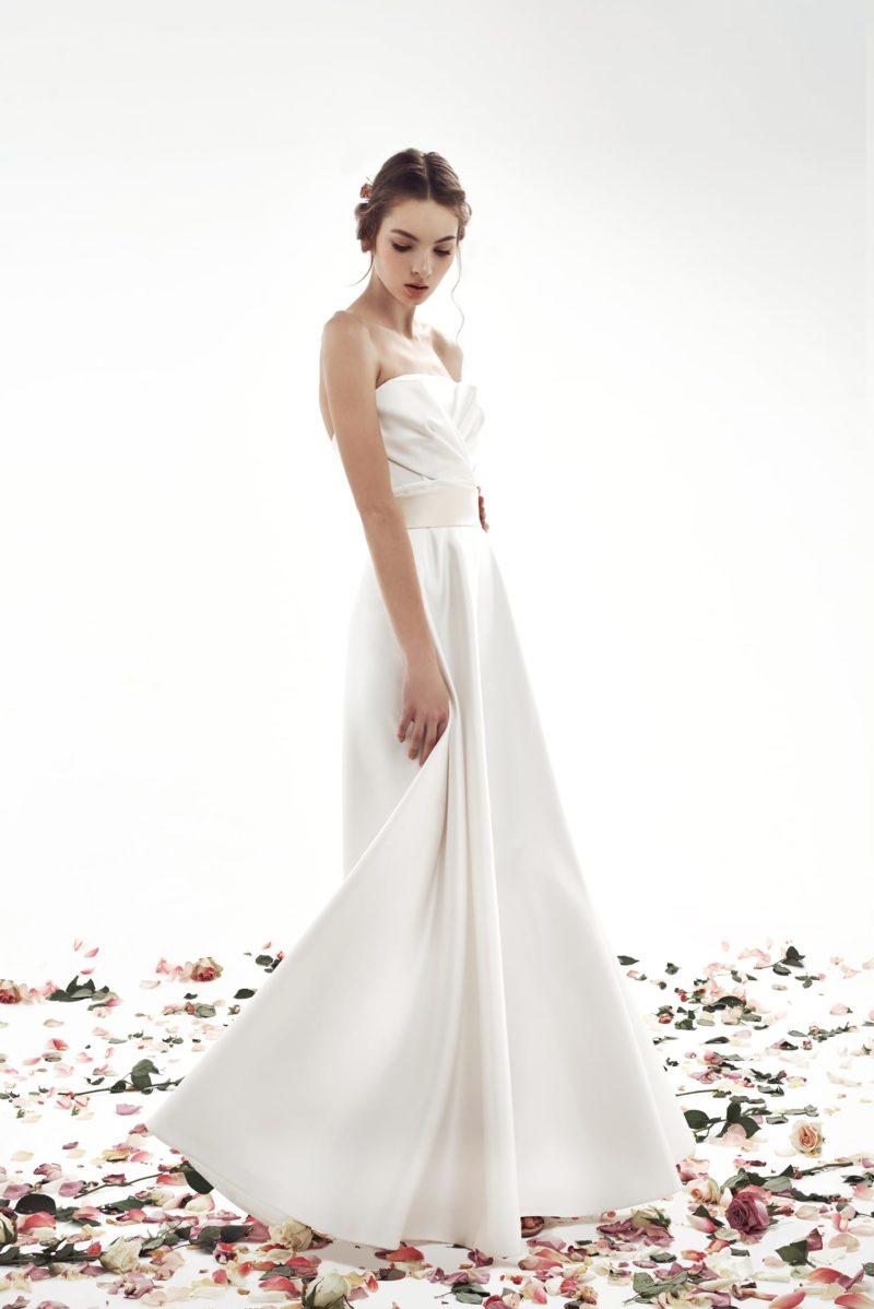 Атласное свадебное платье прямого кроя с изящным широким поясом на талии.