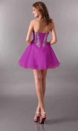 Фиолетовое вечернее платье с пышной юбкой до середины бедра и стразами на лифе.