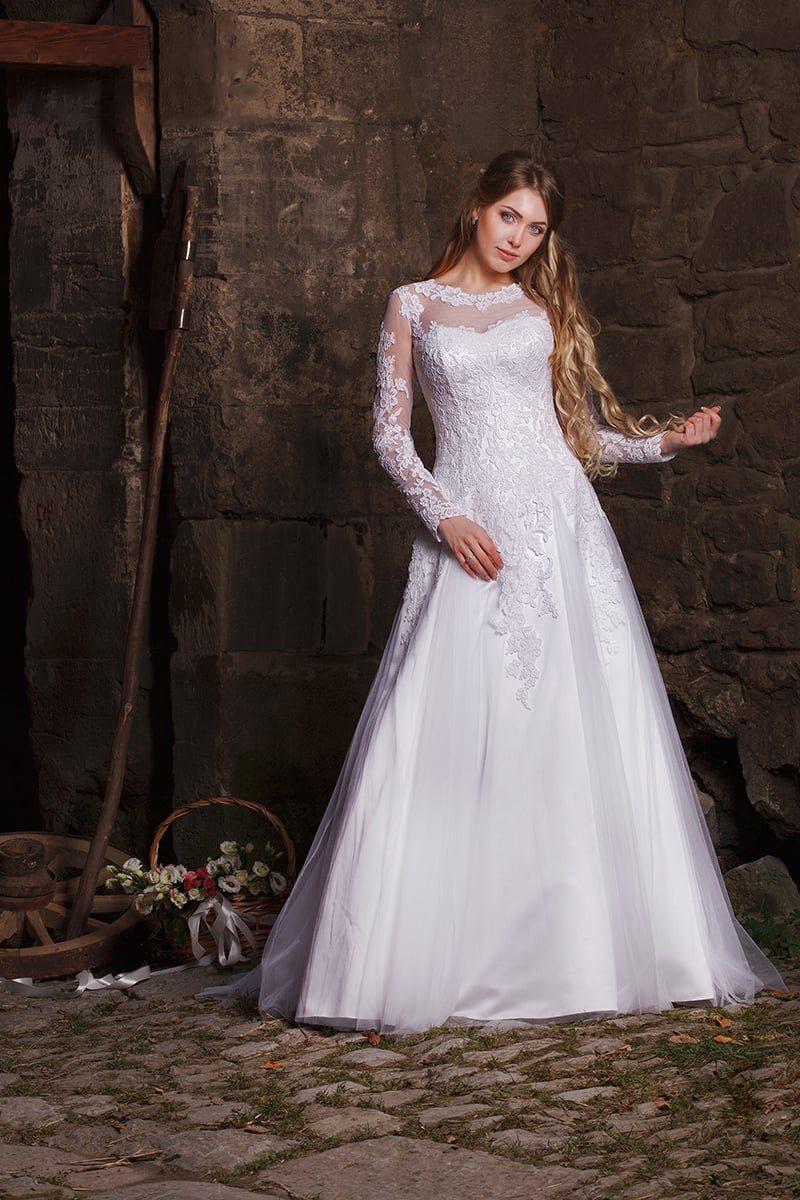 Кружевное свадебное платье силуэта «принцесса» с длинными полупрозрачными рукавами.