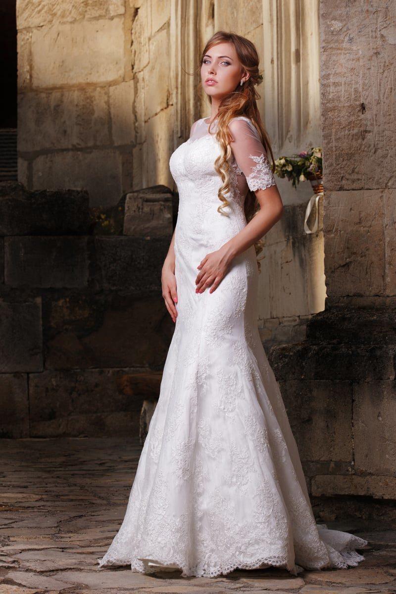 Свадебное платье «рыбка» с кружевной отделкой спинки и короткими прозрачными рукавами.
