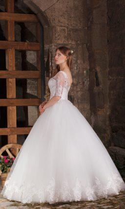Пышное свадебное платье с кружевным корсетом, длинными рукавами и аппликациями по подолу.