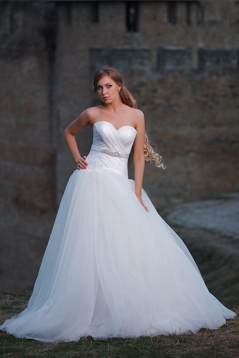 Свадебное платье «трапеция» с облегающим корсетом, покрытым переплетением драпировок.