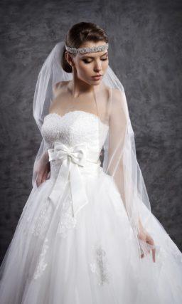 Пышное свадебное платье с кружевным корсетом и сияющим поясом.