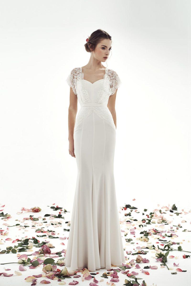 Облегающее свадебное платье с лифом в форме сердца и кружевным рукавом.