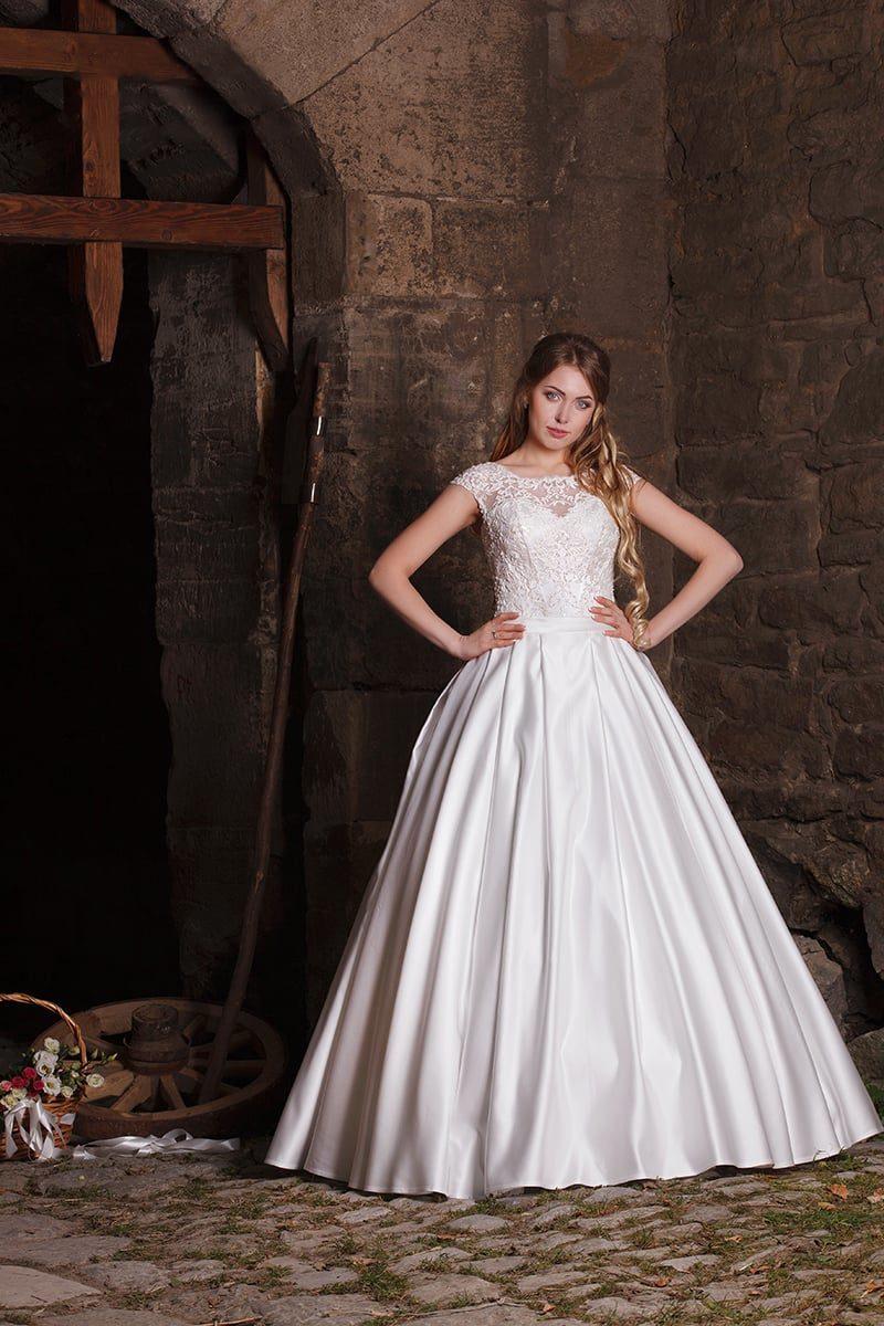 Атласное свадебное платье с закрытым верхом, оформленным тонкой кружевной тканью.