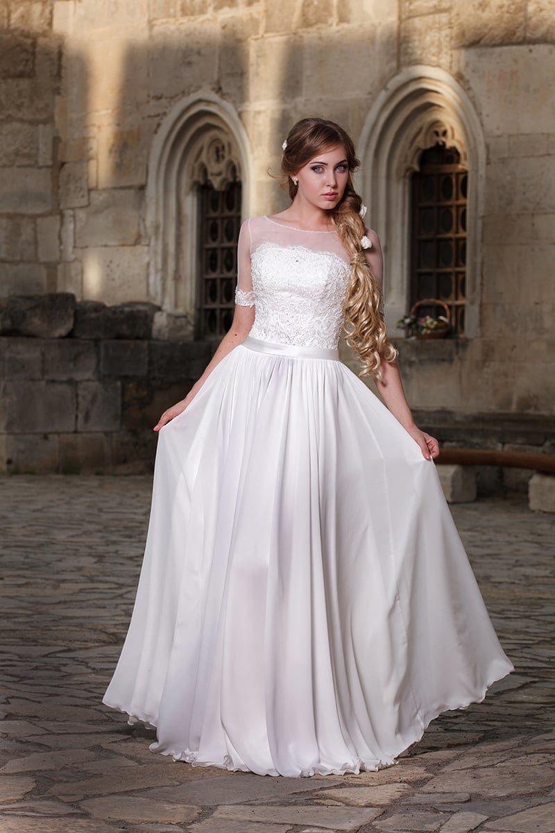 Прямое свадебное платье с округлым вырезом и узким поясом из атласной ткани.