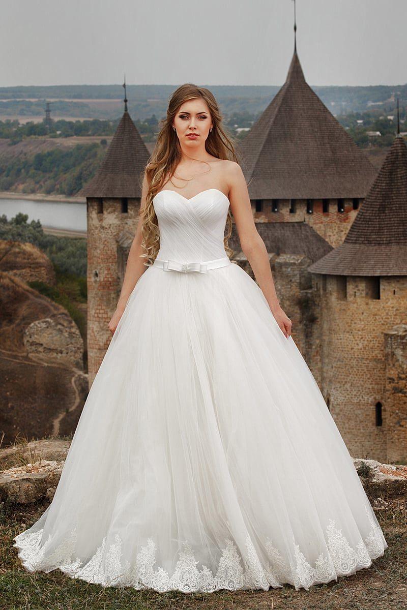 Свадебное платье с изысканной отделкой из драпировок по корсету и многослойной юбкой.