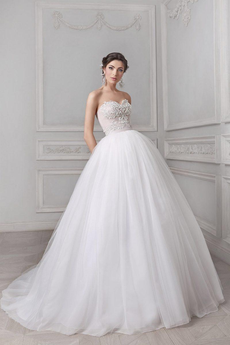 Изысканное свадебное платье с воздушным подолом и открытым корсетом, покрытым кружевом.