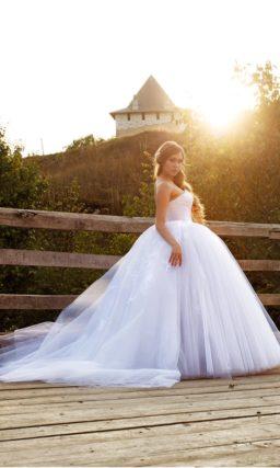 Подчеркнуто пышное свадебное платье с открытым корсетом и длинным объемным шлейфом.