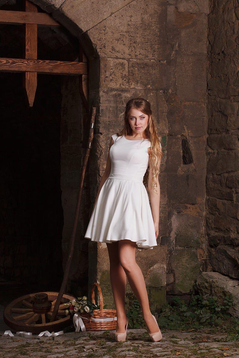 Лаконичное свадебное платье с круглым вырезом и объемной юбкой длиной чуть выше колена.