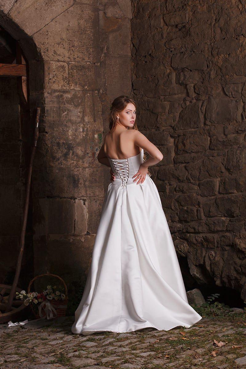 Утонченное свадебное платье из атласной ткани, с узким поясом и укороченным спереди подолом.