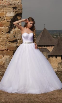 Сдержанное свадебное платье с открытым лифом, сияющим поясом и объемным низом.