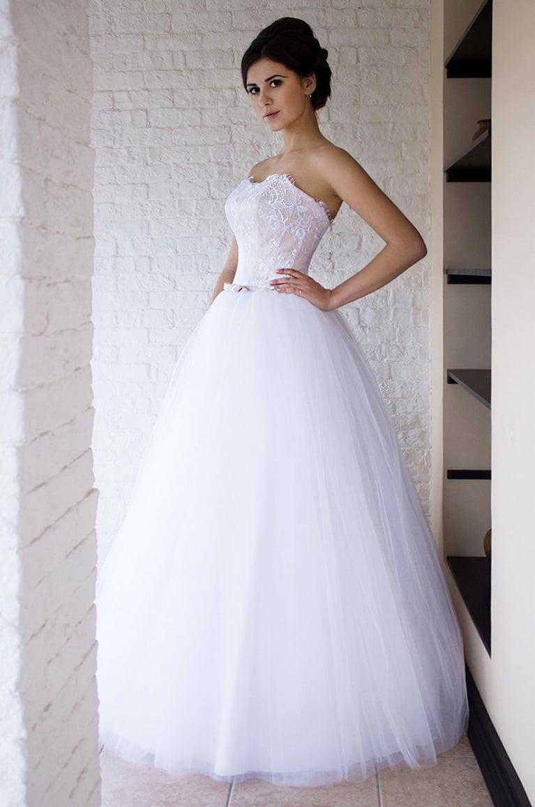 Пышное свадебное платье с открытым корсетом с кружевной отделкой.