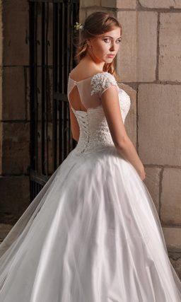 Закрытое свадебное платье с кружевным декором верха и вырезом на спинке.