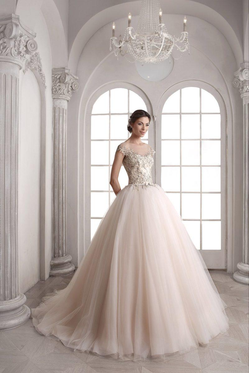Роскошное свадебное платье с пышной юбкой и кружевным верхом, выполненное в оттенке слоновой кости.