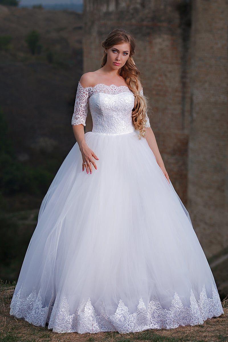 Свадебное платье с атласным лифом и пышной юбкой, украшенное кружевом по верху.