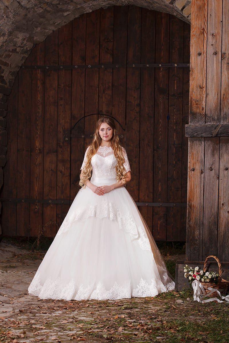 Торжественное свадебное платье с кружевным декором многоярусной юбки и изящным верхом.