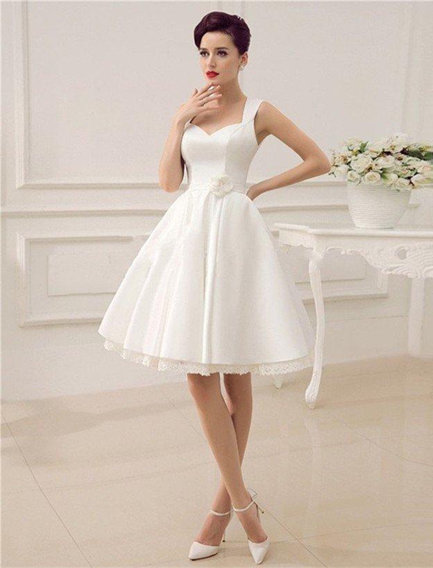 Короткое свадебное платье с многослойной юбкой, украшенной кружевами.