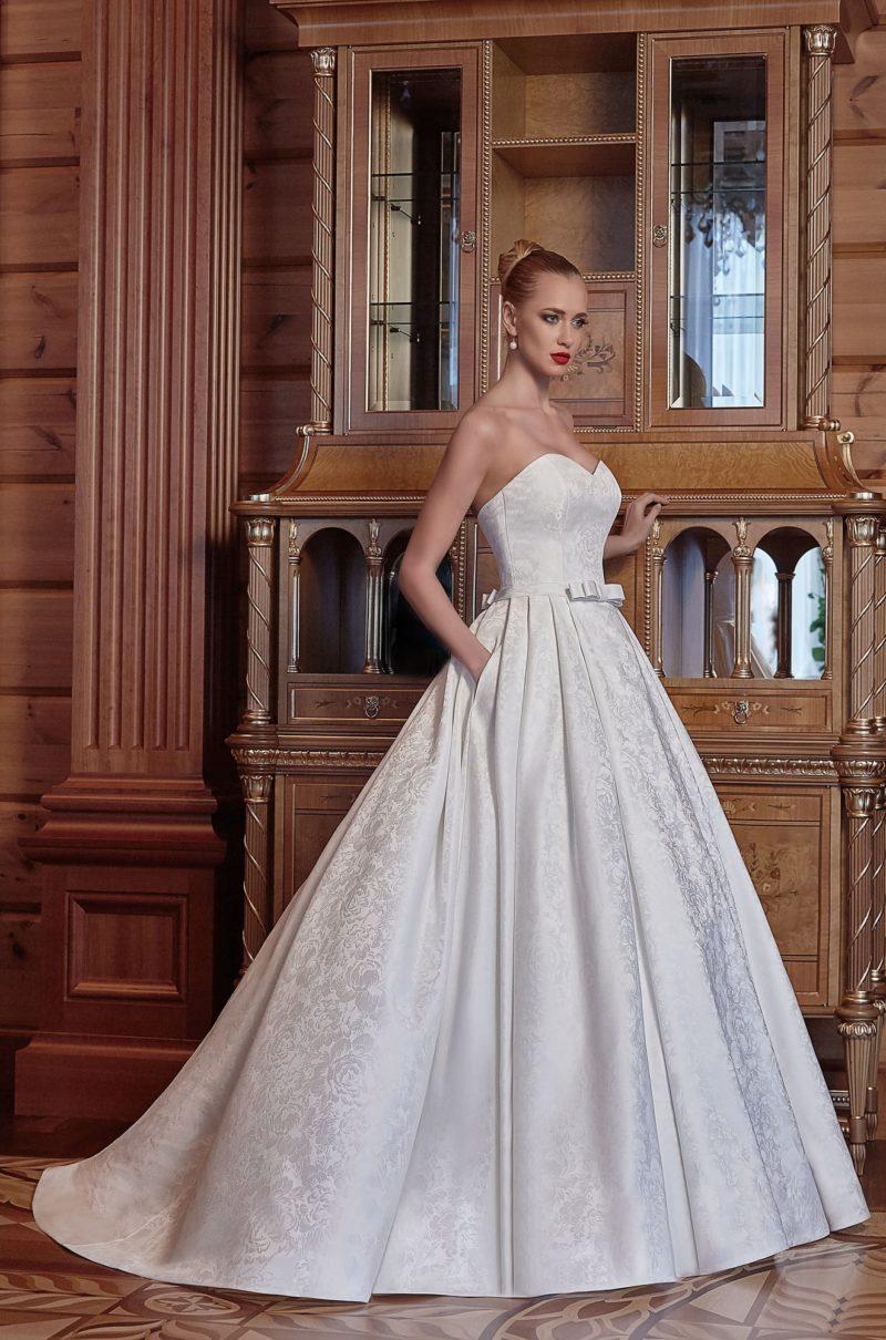 Аристократичное свадебное платье из фактурного атласа с портретным декольте.