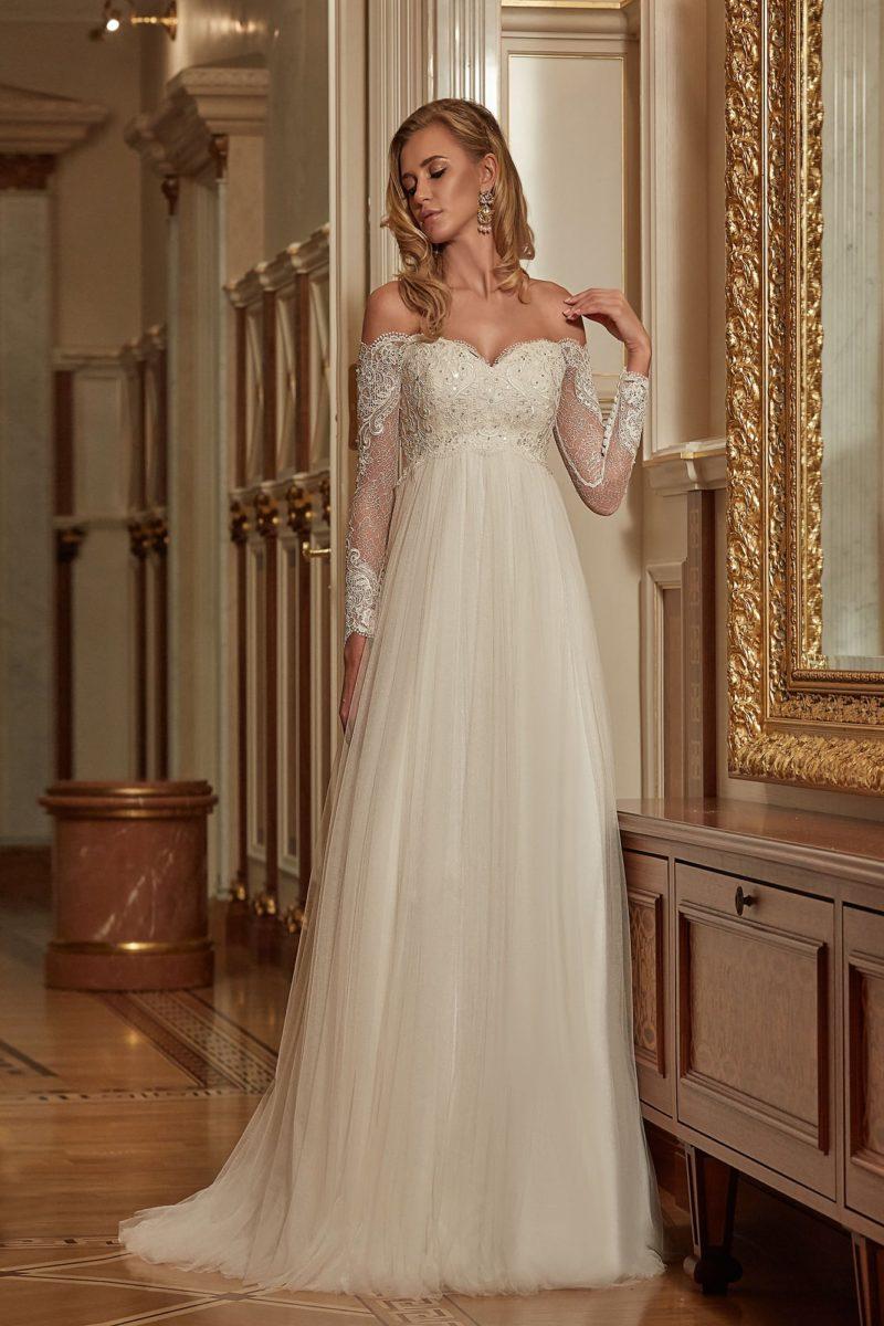 Чувственное свадебное платье, подчеркивающее область декольте портретным вырезом с кружевом.