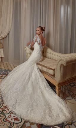 Облегающее свадебное платье, роскошно декорированное кружевом от лифа до длинного шлейфа.