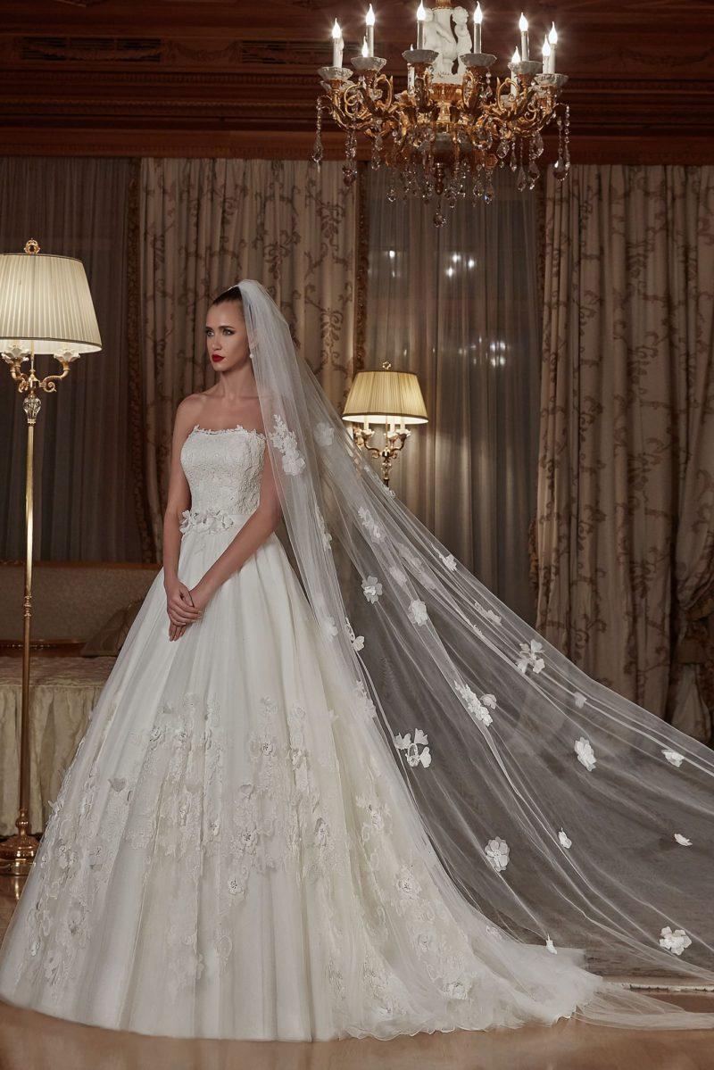 Пышное свадебное платье с открытым корсетом и объемной отделкой по подолу.