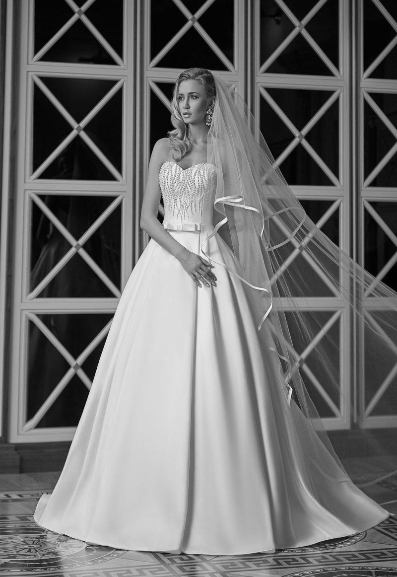 Лаконичное свадебное платье с открытым лифом, украшенным вышивкой из бисера.