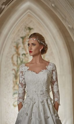 Атласное свадебное платье со скрытыми карманами и фактурной отделкой лифа и рукавов.