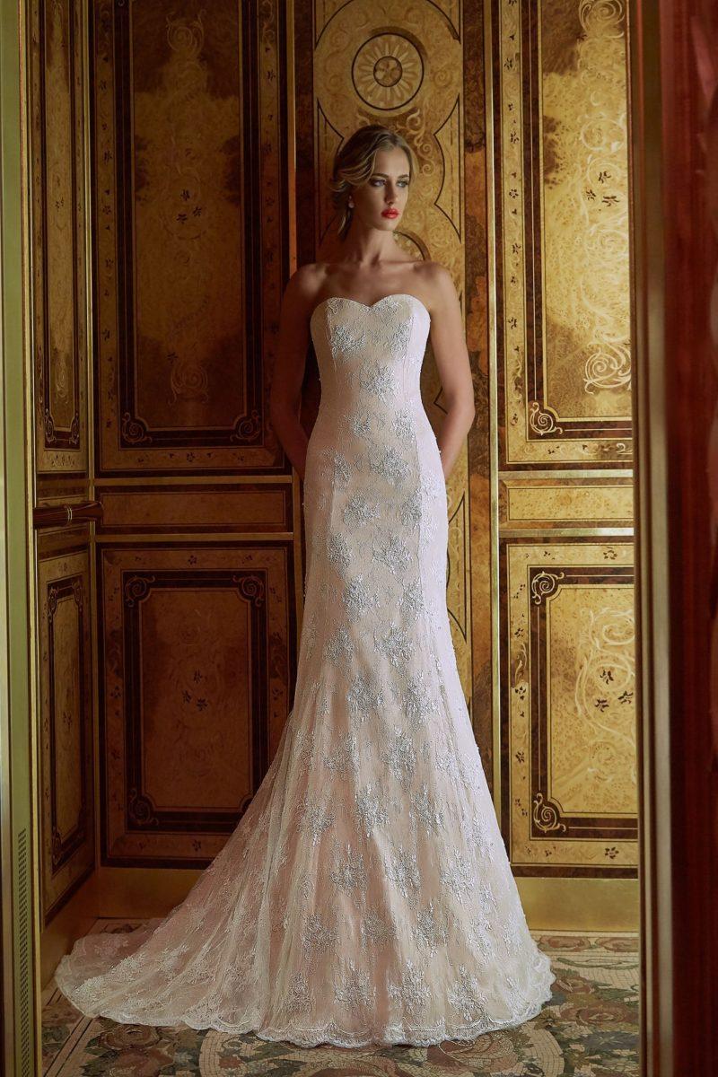 Свадебное платье цвета слоновой кости, облегающее фигуру и украшенное кружевом.